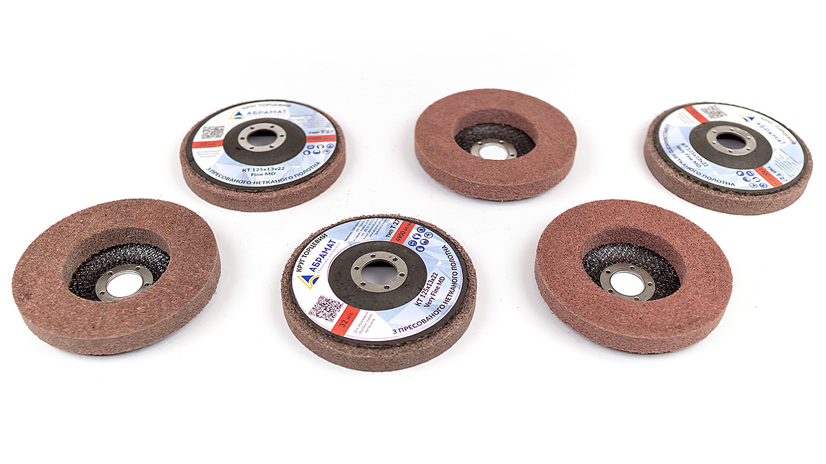 Pressed nonwoven abrasive strip disc
